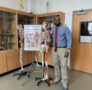 Professor standing next to a skeleton and a diagram.