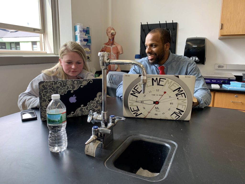 A student and professor sitting together in the lab room.