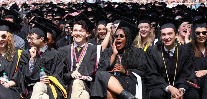 Graduates seated, wearing black academic robes
