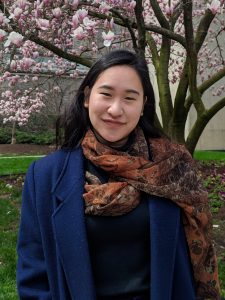 An Asian woman wearing a blue blazer and standing in front of a cherry blossom tree