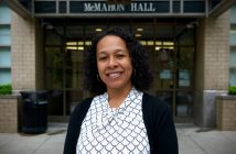 A woman wearing a blouse and a dark cardigan smiles in front of McMahon Hall.