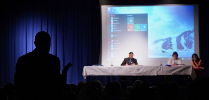 The silhouette of a man facing three panelists at a table