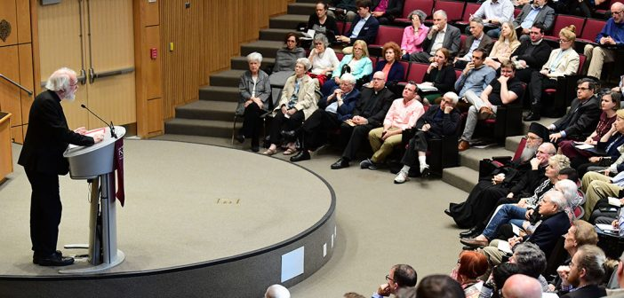 Rowan Williams speaks on stage at the McNally Amphitheatre as audience members look on.