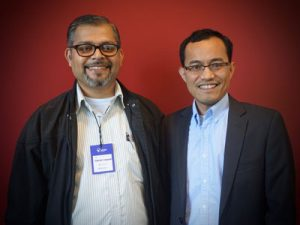 Two men wearing glasses and blazers smile at the camera against a red wall