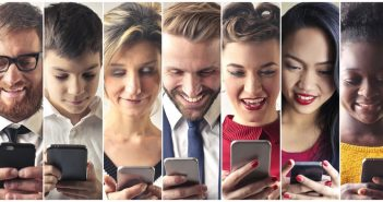 A collage of seven people looking at the their smartphones