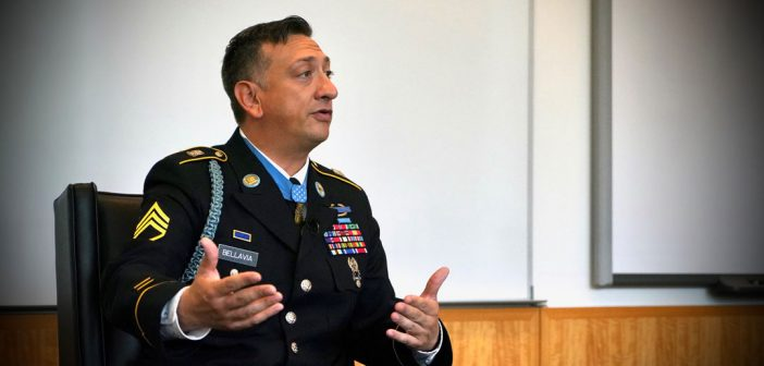 A man wearing a military uniform speaks and gestures towards the side.