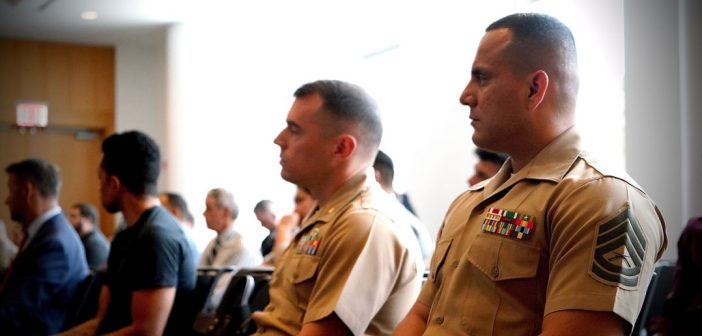 Two men wearing military uniforms sit and look toward the side.