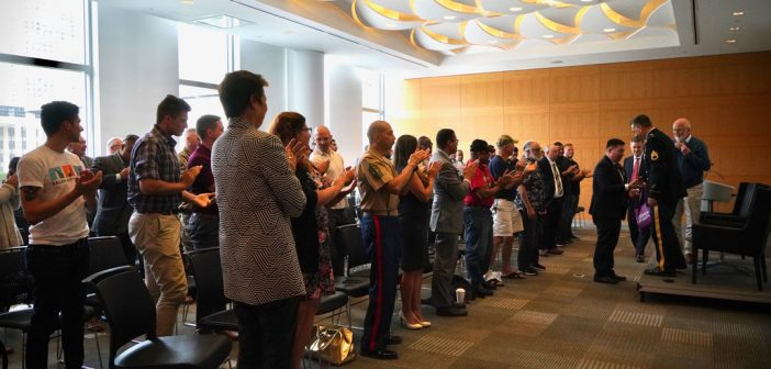 Rows of people stand and applaud for a man wearing a military uniform at the front of the room.
