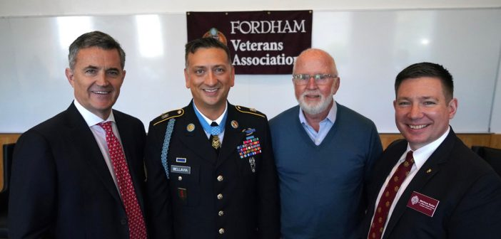 "Four men smile and stand together in front of a flag that says ""Fordham Veterans Association."""