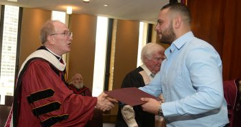 Father McShane congratulates an IDHA graduate.