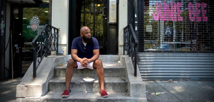 A man sits on a stoop in Harlem.