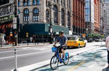 A man riding a bike against a city background