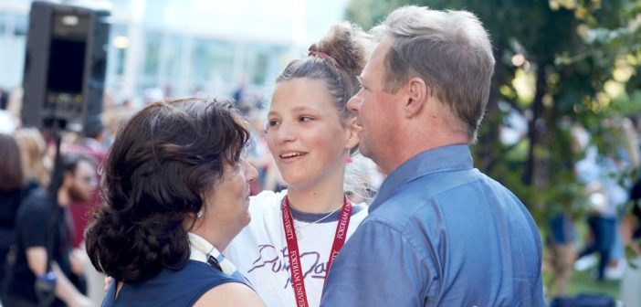 A girl embraces her parents.