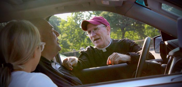 A man wearing a Fordham baseball cap talks to the driver of a car inside his vehicle.