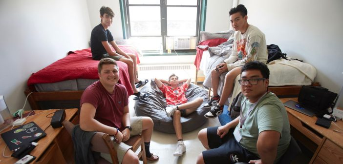 Five young students pose for a picture in a dorm.