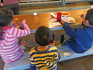 A view of the backs of three migrant children eating in a comedor, or cafeteria, in Nogales, Mexico, March 2019