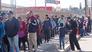 Migrants wait in line for food outside a comedor, or cafeteria, in Nogales, Mexico
