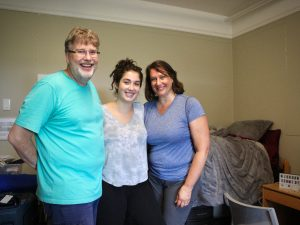 Three people pose for a picture in a dorm room.