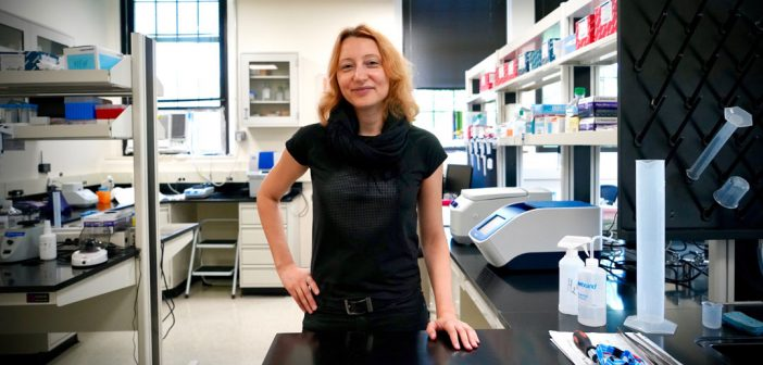 A woman wearing a black outfit stands in the center of a lab.