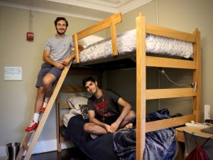 Two boys pose for a photo on a bunk bed.