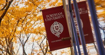 A Fordham flag in front of fall foliage