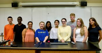 Ten students pose for a group picture in a lab.