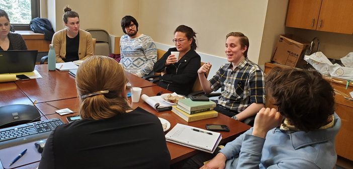 Students sitting around a table talking with faculty