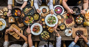 Table set with food and people's hands grabbing for the fare