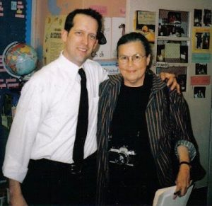 A man and a woman smile at the camera in a classroom.