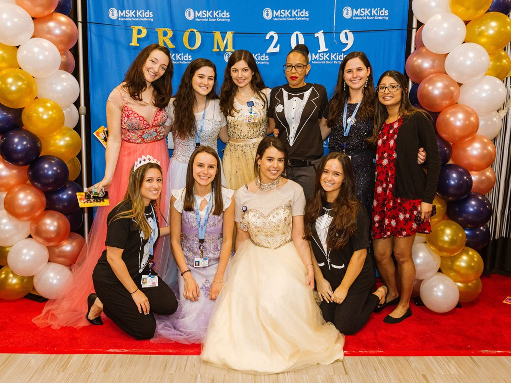 Women pose for a group picture while wearing various colored prom dresses