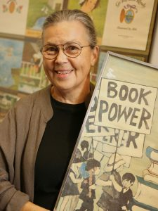 "A woman wearing glasses smiles and holds a photo that says ""BOOK POWER."""