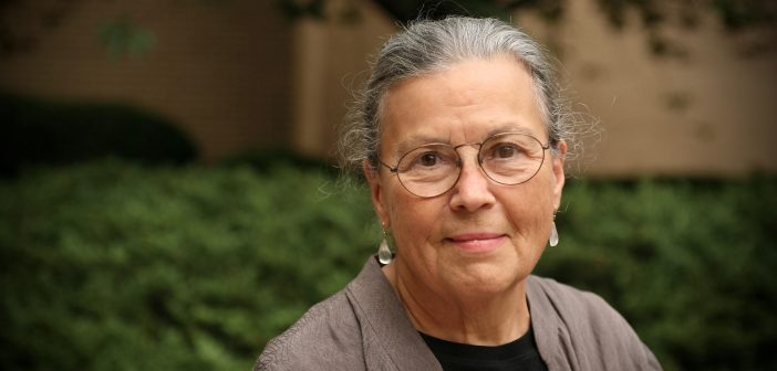 A woman with gray hair and wearing glasses smiles at the camera.