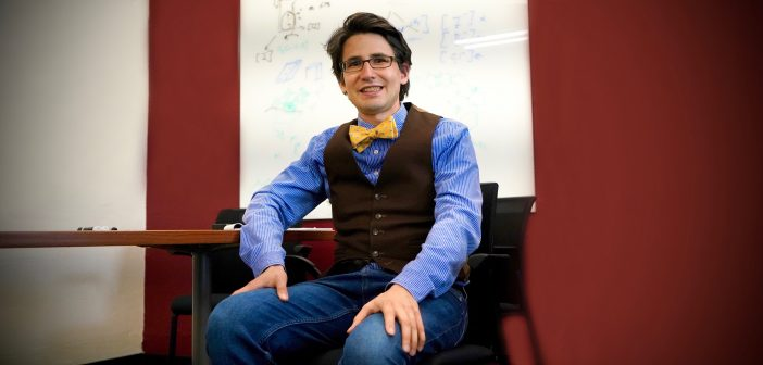 A man wearing a bow tie smiles in a classrooms setting.