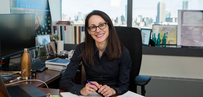 """Fordham Law alumna Danielle Citron, a 2019 recipient of a MacArthur Foundation """"genius"""" grant, sits at her desk at Boston University, where she is a professor of law."""