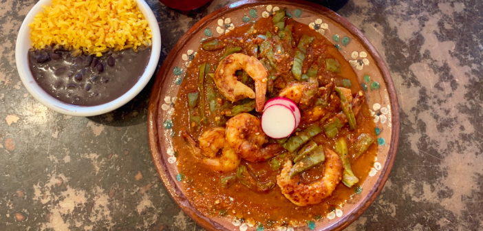 A dish of cactus, shrimp served with rice and beans