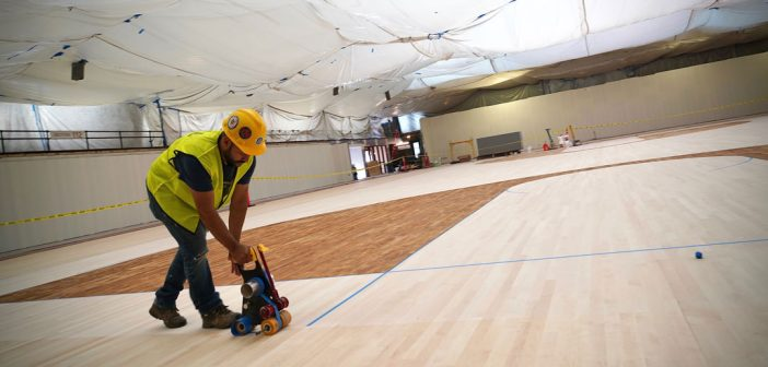 A construction worker moves machinery across a new wooden basketball court floor.