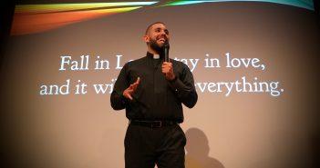 A Jesuit scholastic wearing black garb speaks in front of a PowerPoint presentation slide.