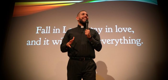 A Jesuit scholastic wearing black garb speaks in front of a PowerPoint presentation slide.