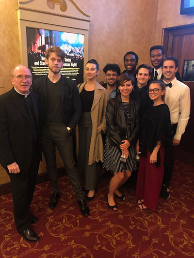 Joseph M. McShane, S.J. (left), president of Fordham, with a group of nine Fordham Theatre students at Crossroads Theatre Company's October 2019 gala honoring Fordham graduate Denzel Washington