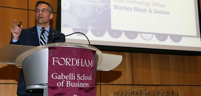 Mark Maybury stands at a podium