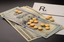 Pills are displayed on top of dollar bills to represent the costs of prescription drugs.
