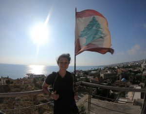Samantha Slattery standing in front of a flag in Lebanon.
