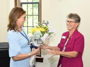 A woman in a pink shirt receives a bouquet of flowers from another woman.