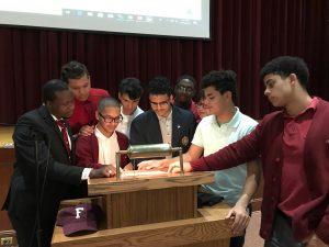 Several men huddled together around a podium