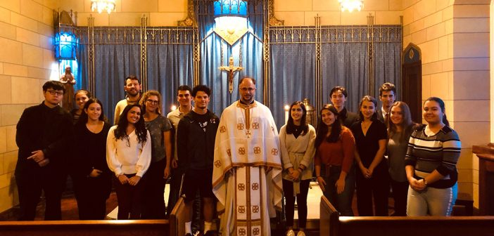 Father Elias Villis, a priest at Christ Our Savior Greek Orthodox Church, stands in the Keating Blue Chapel with students who attended a service there.