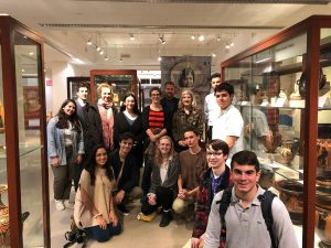 Students standing together in front of museum exhibit cases.