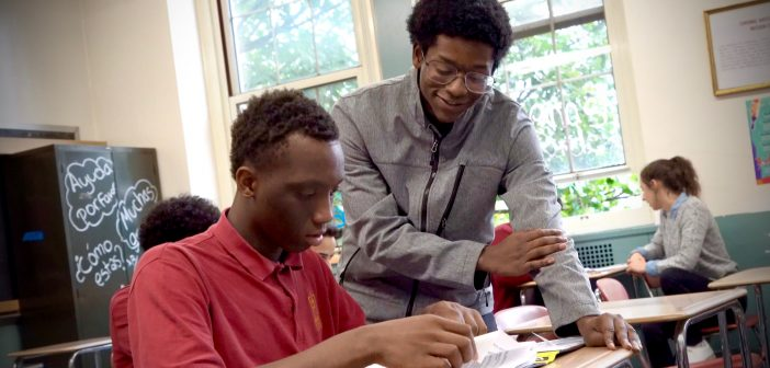 A student stands above a seated student, helping him with his studies.