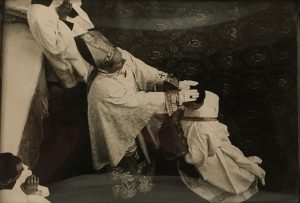 priest with a hands being laid on his head