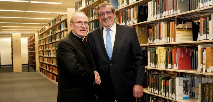 Father McShane and Michale Dowling standing together in front of books.