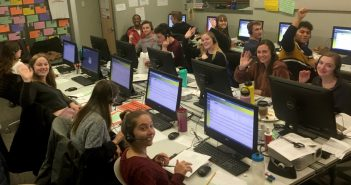 Students sitting in front of computers, wearing headsets and smiling at the camera